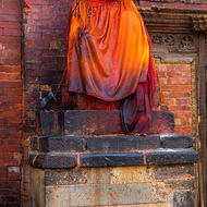 Heavily anointed image in the old city of Patan.