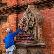 Man anointing image in the old city of Patan.