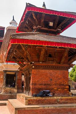 Thumbnail image ofMan sleeping at the base of a pagoda.