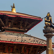 Top tier of a pagoda and statue with pigeons.