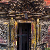 Ornate carved doorway and locked door.
