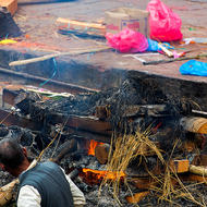 Final tending of a cremation fire before the ashed are cast over the Bagmati River.