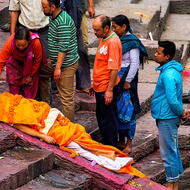 Body of a recently deceased undergoes the ritual washing beside the Bagmati River at the Pashupati temple.