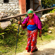 C'mon, smile.  Local woman walking with trekking pole.