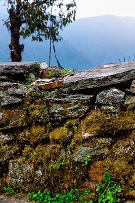 Thumbnail image of Mossy stone fence and misty mountains.