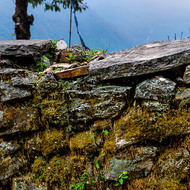 Mossy stone fence and misty mountains.