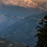 Prayer flags strung out across the vista of the Annapurna Range at sunrise.