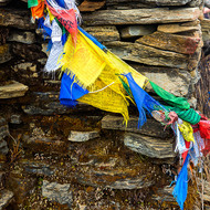 A tangle of prayer flags around a fence.
