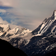 Annapurna Range in late afternoon as darkness settles over the valleys and the last of the sun catches the peaks.