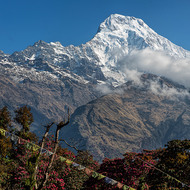 Clear blue sky behind the Annapurna Range, clouds in front.