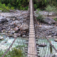 Porter crossing a long suspension bridge over the Modi Khola.