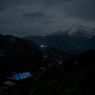 Moonlight on a house roof and lights in the valley.