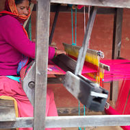 Woman in pink at weaving loom.