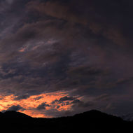 Panorama of the mountains after the sun has set and heavy clouds start to clear.