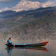 Boating on Lake Phewa, the Annapurna Range as backdrop.