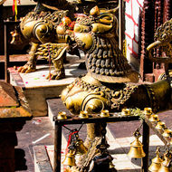 Pair of guardian lions in front of the central pagoda at Taal Barahi temple.