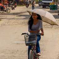 Young woman, with umbrella, riding a bicycle.