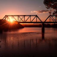 Rail bridge over the Bellinger River at sunset.