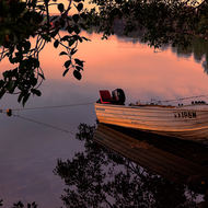 Small fishing dinghy on the Bellinger River in early morning light.