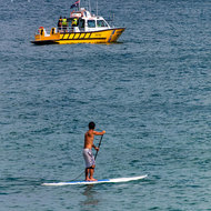 Stand-up paddle boarder watches a coast guard vessel manoeuvre.