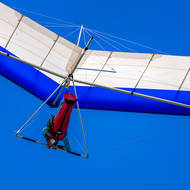 Hang glider checks his cell.