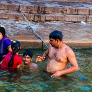 Family bathing at dawn in the sacred River Ganges.