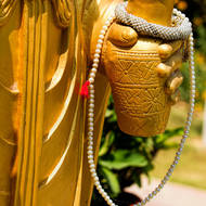 Buddha statue hand and beads.