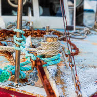 Assortment of rope and chains on boat bow deck.