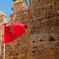 Flag of morocco flies outside the turreted walls of the ancient ruins of Chellah.