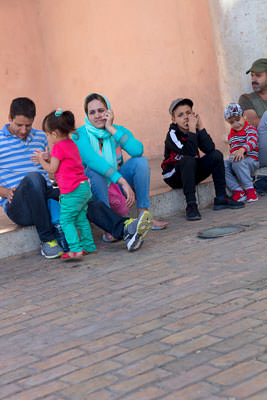 Thumbnail image of Family sitting at the Bab el-Mansour gate.