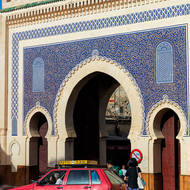 Gateway into old Fes with little red taxi doing a drop-off.