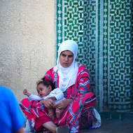 Sitting, mother and child, outside a mosque.