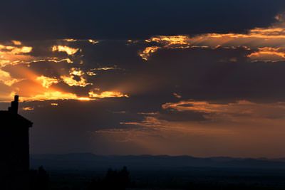 Thumbnail image ofSun setting flares through clouds.