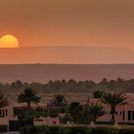 Sun rises past the low mountains and the western Sahara Desert.
