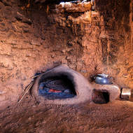 Rock and adobe cooking enclosure with oven.