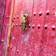 Magenta door and hand of Fatima knocker.