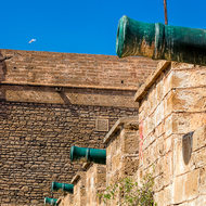 Four green cannon sitting on the wall.