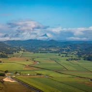 Mt Warning appears from the clouds beyond the lush Tweed valley.