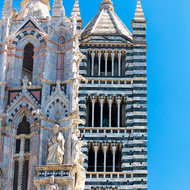 White and green banded tower of the Duomo of Siena.