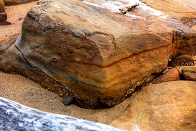 Thumbnail image of Banded sediment boulder on beach.