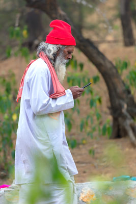 Thumbnail image ofSadhu, holy man, on cell phone.