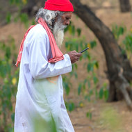 Sadhu, holy man, on cell phone.