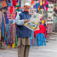 Market vendor catching up on the news during a lull in trade.