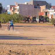 Boys playing cricket in waste ground.