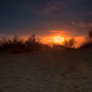 Sun sets over the sand dune.