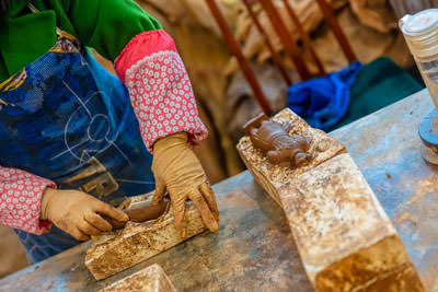 Thumbnail image ofArtisan pressing clay to moulds for miniature...