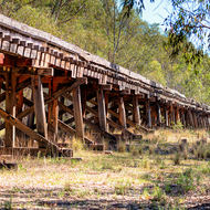 Timber truss railroad viaduct over dry creek bed.